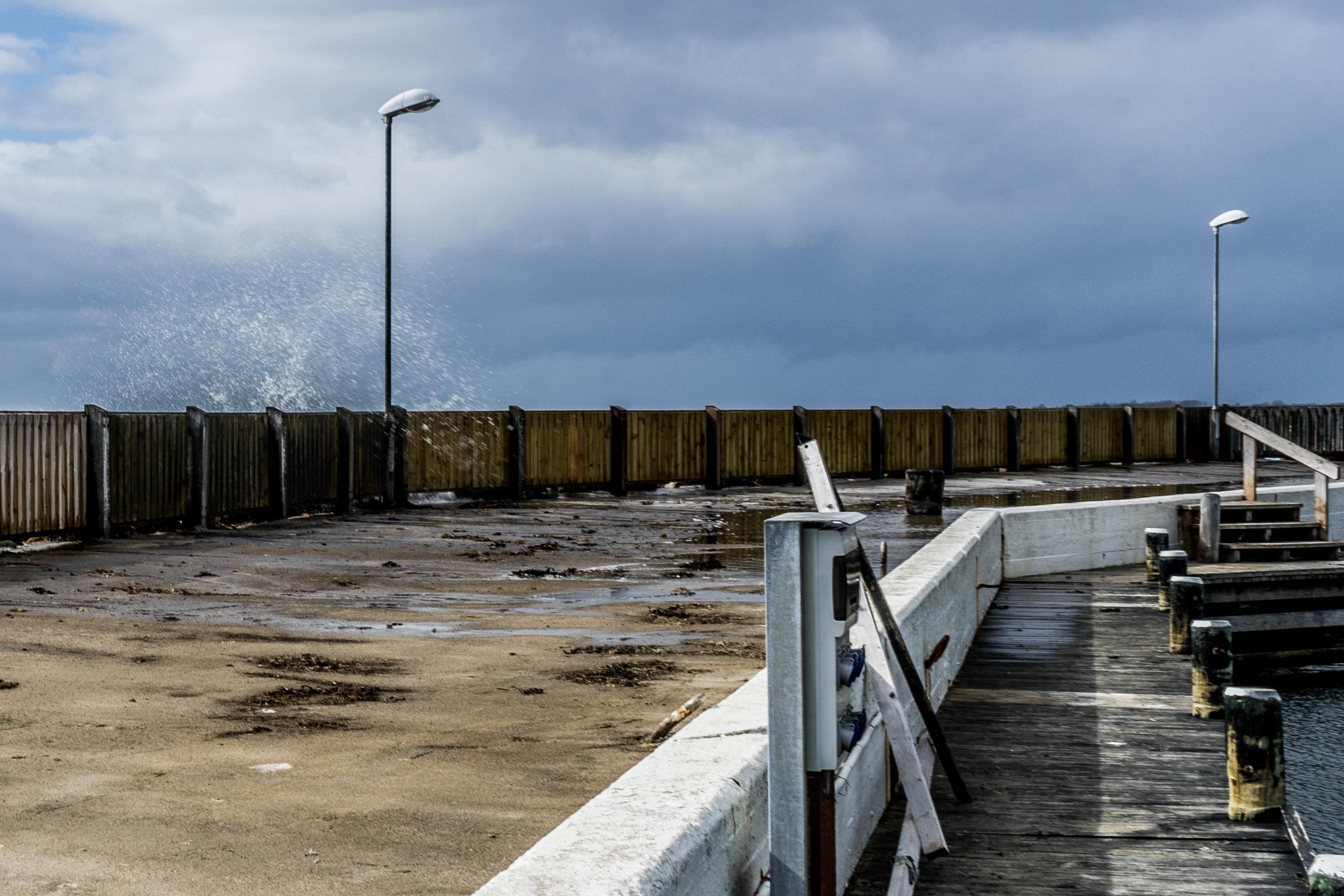 Gischt spritzt über die Hafenmole