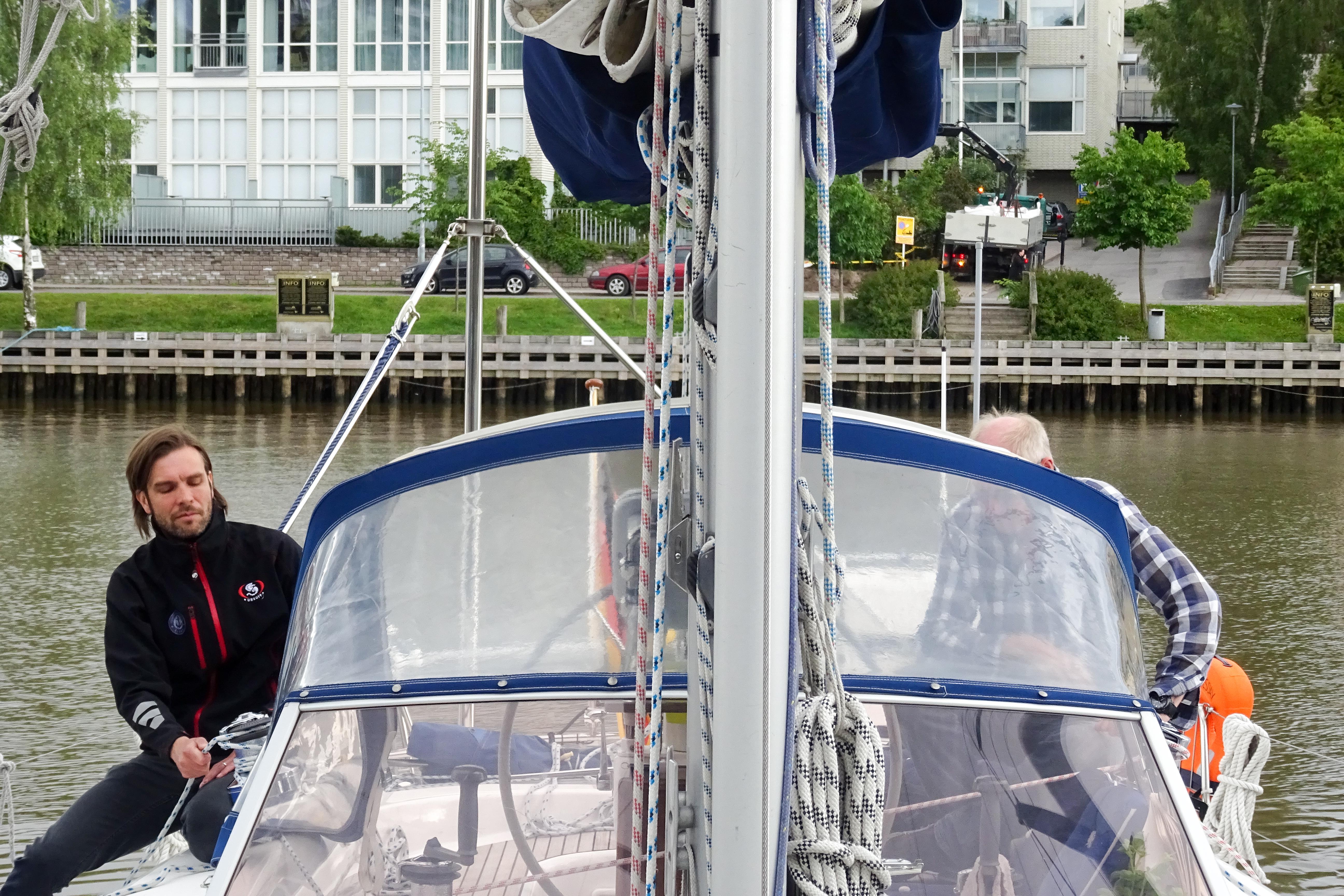 Toni, der Hafenmeister und Peter warten darauf, den jungen Mann wieder vom Mast herunter zu lassen